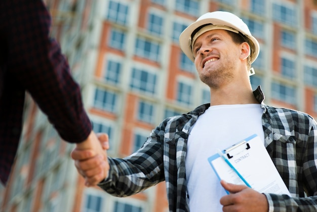 Close-up, vista de ângulo baixo do engenheiro e arquiteto apertando as mãos