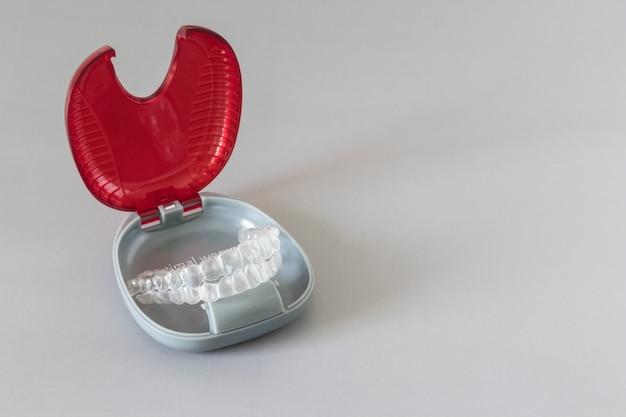 Close-up vista de aparelho invisalign ou retentores invisíveis em fundo cinza