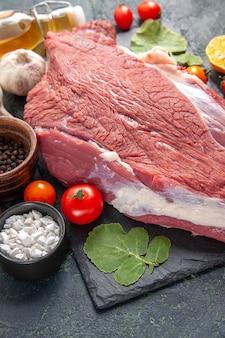 Close-up vista de carne vermelha crua fresca na bandeja preta pimenta vegetais caídos faca de garrafa de óleo em fundo de cor escura