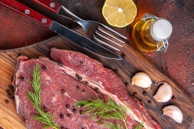 Close-up vista de carne vermelha em tábua de corte de madeira e garrafa de alho oi pimenta verde e faca em imagem de fundo escuro
