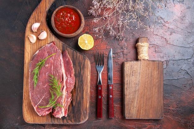 Close-up vista de carne vermelha em uma tábua de madeira e ketchup em uma tigela pequena garfo e faca em fundo escuro
