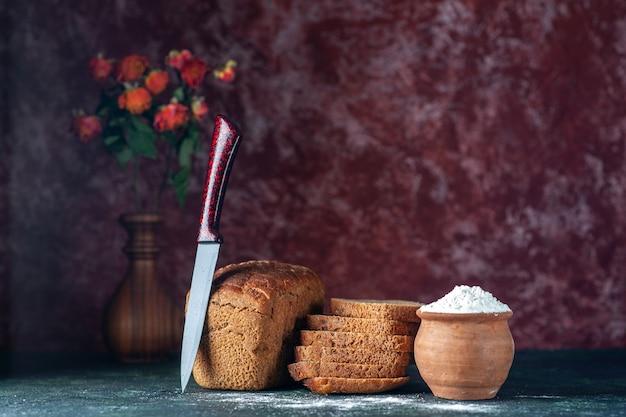 Close-up vista de corte inteiro de pão preto dietético e farinha de faca em vaso de flores tigela sobre fundo de cores marrons azul