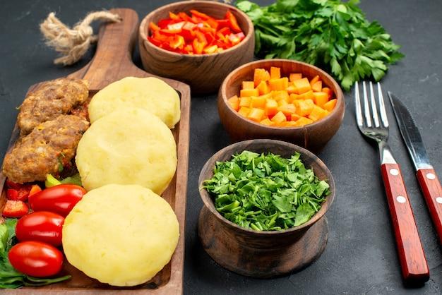 Close-up vista de costeletas saborosas com legumes com garfo e faca no escuro