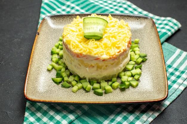 Close-up vista de deliciosa salada servida com pepino picado em toalha verde despojada meio dobrada em fundo escuro