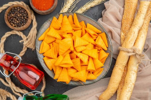 Close-up vista de deliciosas batatas fritas caídas de garrafas pimentas na toalha e corda em um fundo preto