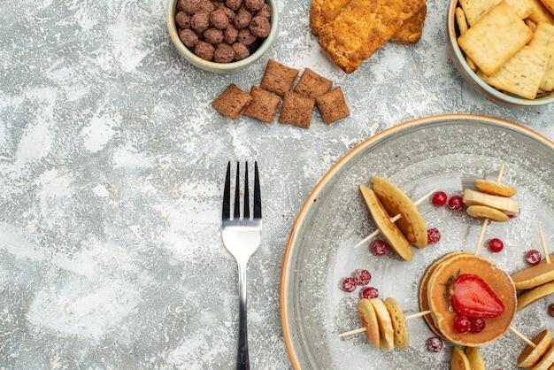 Close-up vista de deliciosas panquecas com chocolate e biscoitos no azul