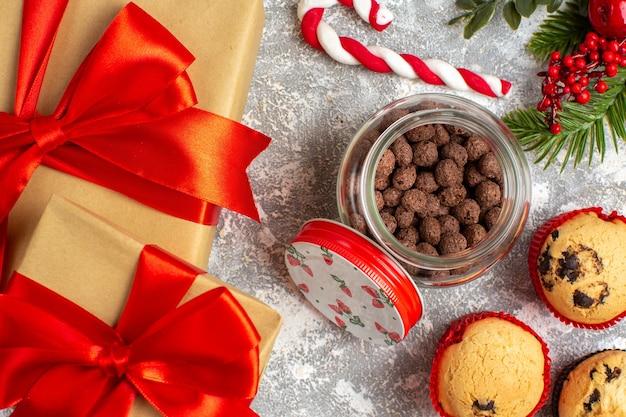Close-up vista de deliciosos bolinhos pequenos e chocolate em uma panela de vidro e ramos de abeto ao lado do presente com fita vermelha na superfície do gelo