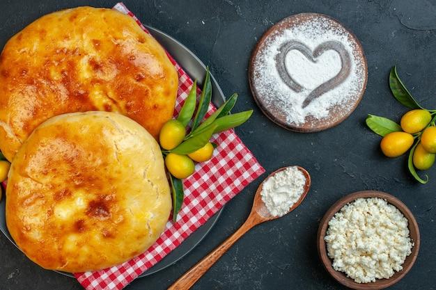Close-up vista de deliciosos kumquats pastéis recém-assados com o caule em uma toalha vermelha despojada e farinha de queijo em forma de coração em uma tábua de corte em um fundo escuro