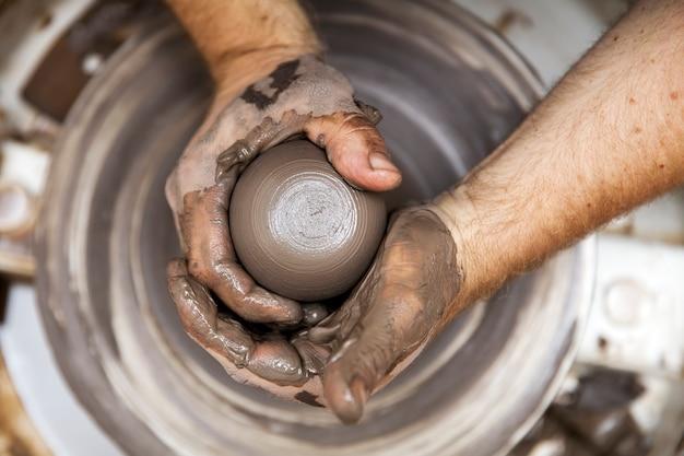Close-up vista de detalhe em um artista faz cerâmica de barro em uma roda de giro