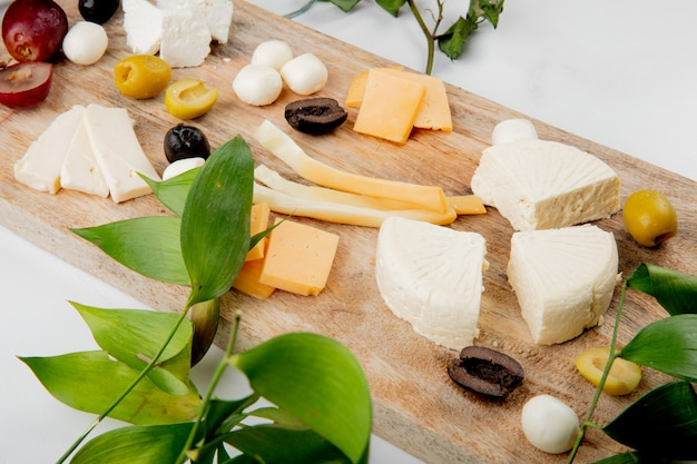 Close-up vista de diferentes tipos de queijo com pedaços de uva azeitonas na tábua em branco decorado com folhas