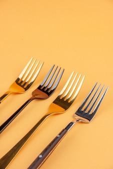 Close-up vista de elegantes garfos de aço inoxidável brilhantes em fundo dourado isolado com espaço livre