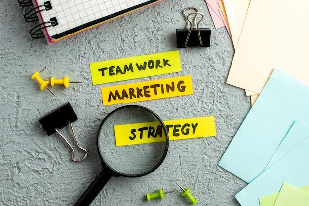 Close-up vista de envelopes coloridos e escritos de estratégia de marketing de trabalho em equipe no caderno espiral de lupa sobre fundo de areia cinza