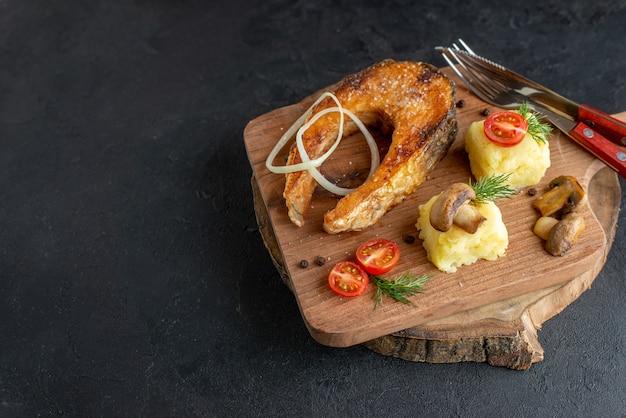 Close-up vista de farinha de peixe frito com cogumelos, vegetais, queijo e talheres em uma placa de madeira no lado esquerdo na superfície preta angustiada