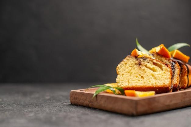 Close-up vista de fatias de bolo macio recém-assado na tábua de madeira na mesa escura