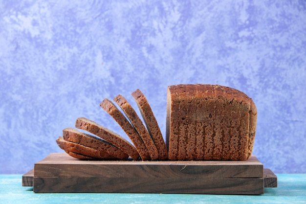 Close-up vista de fatias de pão preto cortadas ao meio em tábuas de madeira sobre fundo azul claro