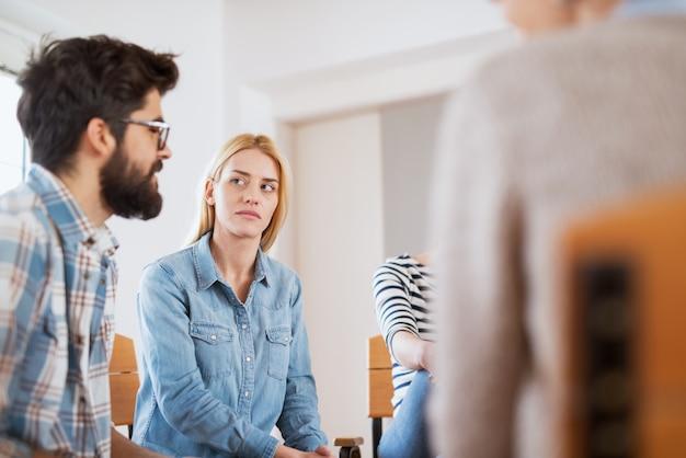 Close-up vista de foco de preocupada mulher estressada enquanto ouve um dos pacientes em terapia de grupo especial.