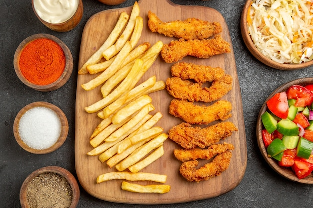 Close-up vista de frango frito, batata, temperos diferentes e chucrute com salada na mesa escura