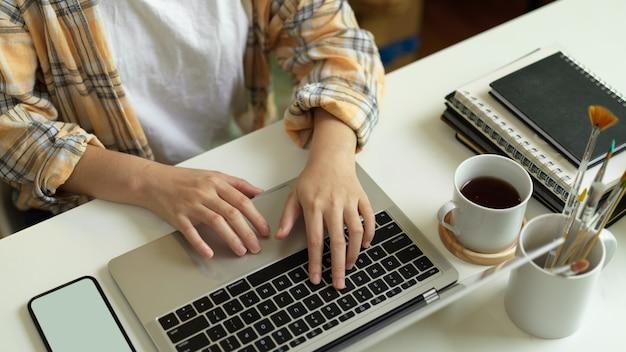 Close-up vista de freelancer feminino nas mãos de jaqueta scott, digitando no teclado do laptop na mesa do escritório com a xícara de café