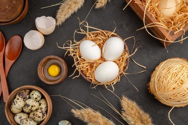 Close-up vista de garras amarelas em uma caixa de madeira corda espetando ovos em fundo preto