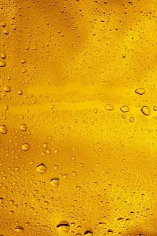 Close-up vista de gotas de frio no copo de fundo de cerveja. textura de refrigerante de bebida alcoólica com macro bolhas na parede de vidro. fizzing ou flutuando até o topo da superfície. de cor dourada.