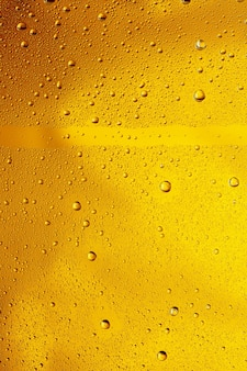 Close-up vista de gotas frias no copo de fundo de cerveja. textura de refrigerante de bebida alcoólica com macro bolhas na parede de vidro. fizzing ou flutuando até o topo da superfície. de cor dourada.