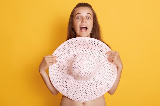 Close-up vista de jovem atônita com a boca amplamente aberta, cobrindo os seios com chapéu de palha