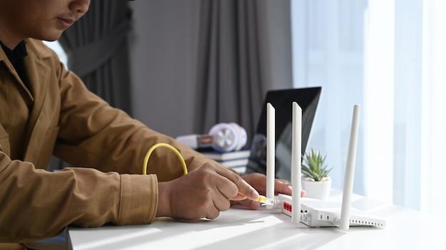 Close-up vista de jovem conecta o cabo de internet no roteador sem fio em casa.