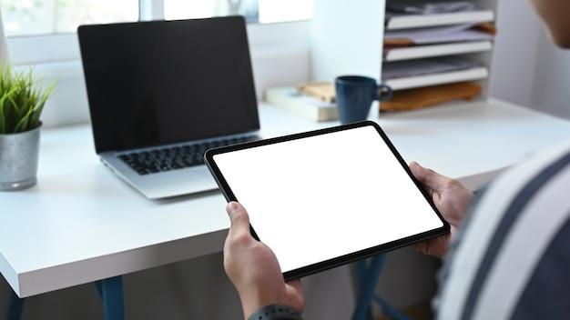 Close-up vista de jovem freelance trabalhando com laptop e usando tablet digital no escritório em casa