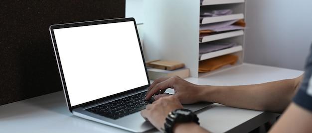 Close-up vista de jovem trabalhando em um computador laptop em um local de trabalho confortável