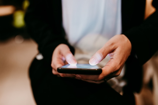 Close-up vista de jovem usando telefone celular em um café ou restaurante dentro de casa. estilos de vida irreconhecíveis