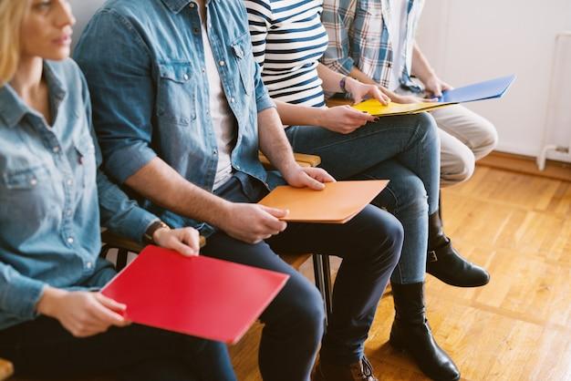 Close-up vista de jovens sentados em cadeiras com pastas antes da entrevista de emprego na sala de espera.