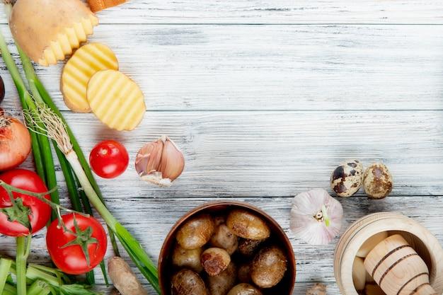 Close-up vista de legumes como alho cebolinha ovo tomate com batatas assadas na tigela sobre fundo de madeira com espaço de cópia