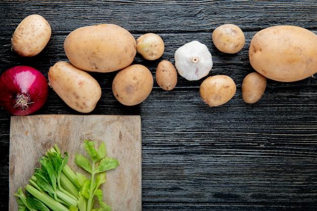 Close-up vista de legumes como alho de batata cebola com aipo cortado na tábua sobre fundo de madeira com espaço de cópia