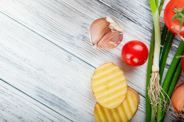 Close-up vista de legumes como alho fatiado tomate batata e cebolinha no lado direito e fundo de madeira com espaço de cópia