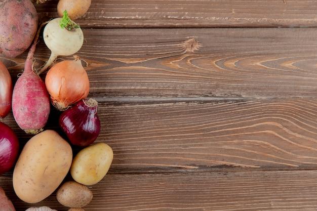 Close-up vista de legumes como batata de cebola rabanete em fundo de madeira com espaço de cópia