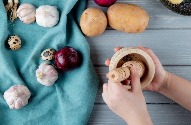 Close-up vista de legumes como cebola alho ovo batata com mão de mulher pressionando grãos de pimenta preta no triturador em fundo de madeira