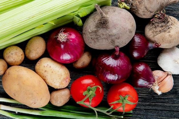 Close-up vista de legumes como tomate de cebola beterraba aipo batata e outros em fundo de madeira