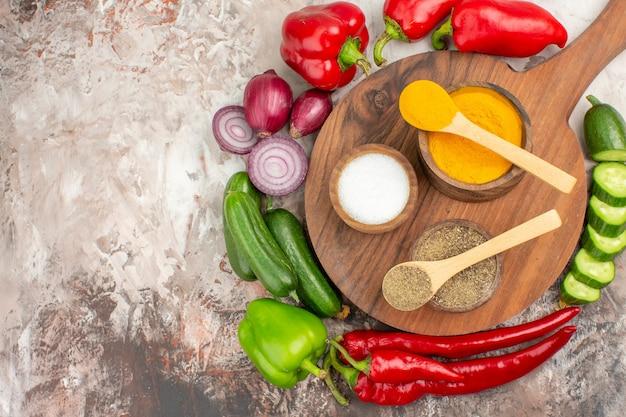 Close-up vista de legumes frescos inteiros e picados e especiarias diferentes