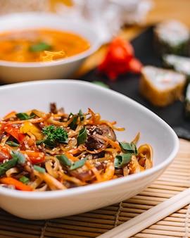 Close-up vista de macarrão asiático frito com pimentão e cebola em uma tigela
