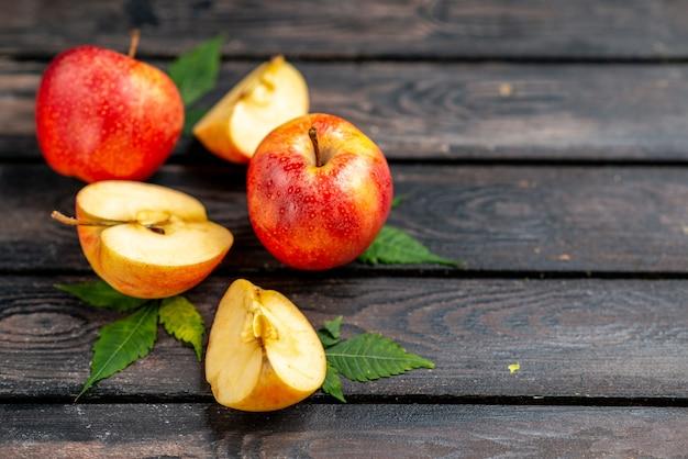 Close-up vista de maçãs frescas naturais cortadas e inteiras vermelhas e folhas em fundo preto