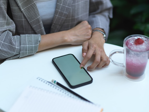 Close-up vista de mãos femininas tocando no smartphone na mesa de centro com bebida e caderno no café