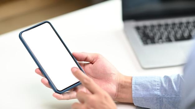 Close-up vista de mãos masculinas digitando no celular com espaço em branco vazio para anunciar o texto.