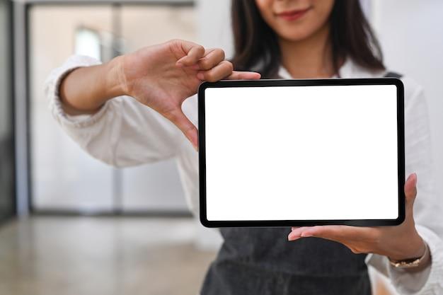 Close-up vista de mulher feliz barista mostrando tablet digital com tela em branco em pé no café.
