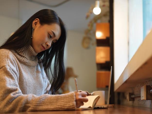 Close-up vista de mulher tomando nota enquanto trabalha com simulação de laptop no balcão de madeira de um café