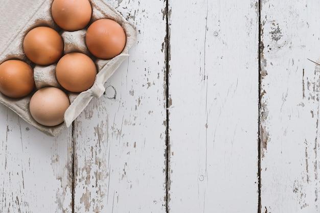 Close-up vista de ovos de galinha em caixa de ovo no fundo de madeira branco