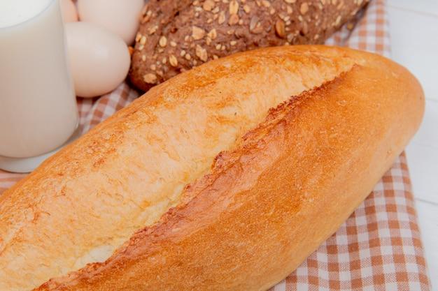 Close-up vista de pães como baguete preta e vietnamita com leite de ovos no pano xadrez e mesa de madeira