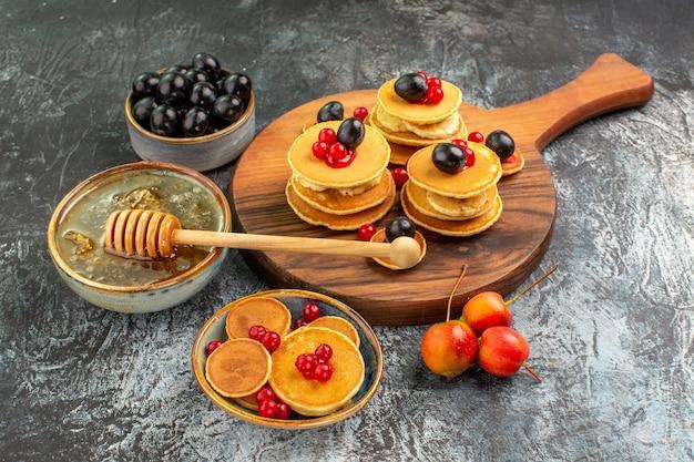 Close-up vista de panquecas clássicas na tábua de mel e frutas