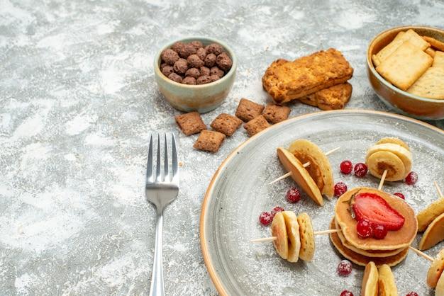Close-up vista de panquecas de leitelho na tábua com chocolate e biscoitos no azul