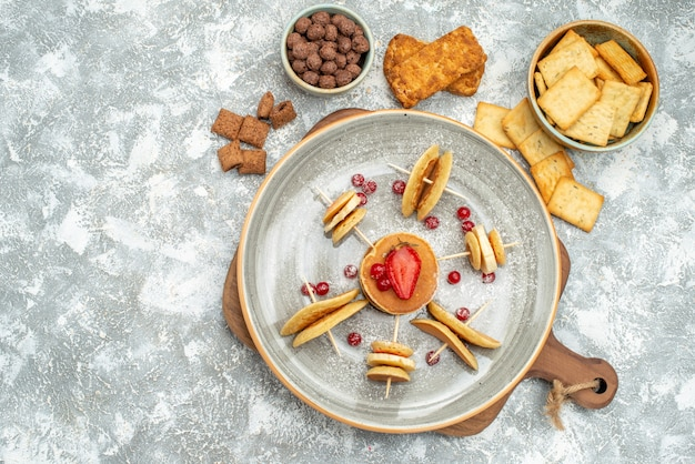 Close-up vista de panquecas e biscoitos caseiros na tábua de madeira no azul