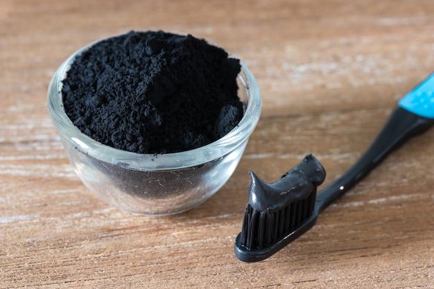 Close-up vista de pasta de dente de carvão preto e fundo de madeira de íon escova de dente